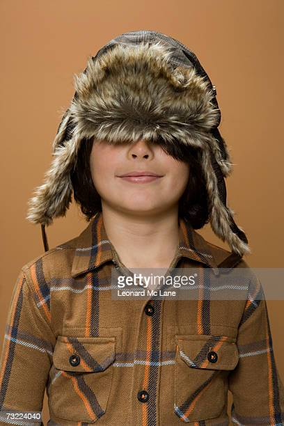 Boy (8-9) with hat covering eyes, smiling, close-up