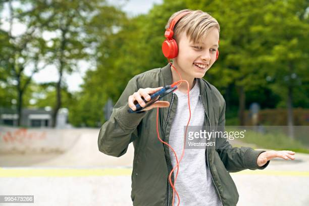 boy with headphone dancing while listing to music on smartphone - groove stock photos and pictures