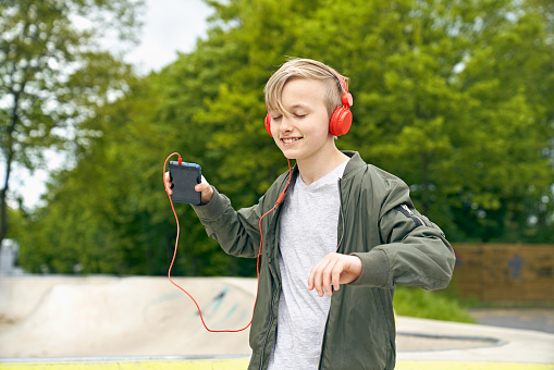 Boy with headphone dancing while listing to music on smartphone - gettyimageskorea