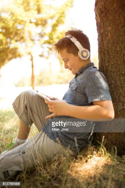 Boy with headphones listening to music in park