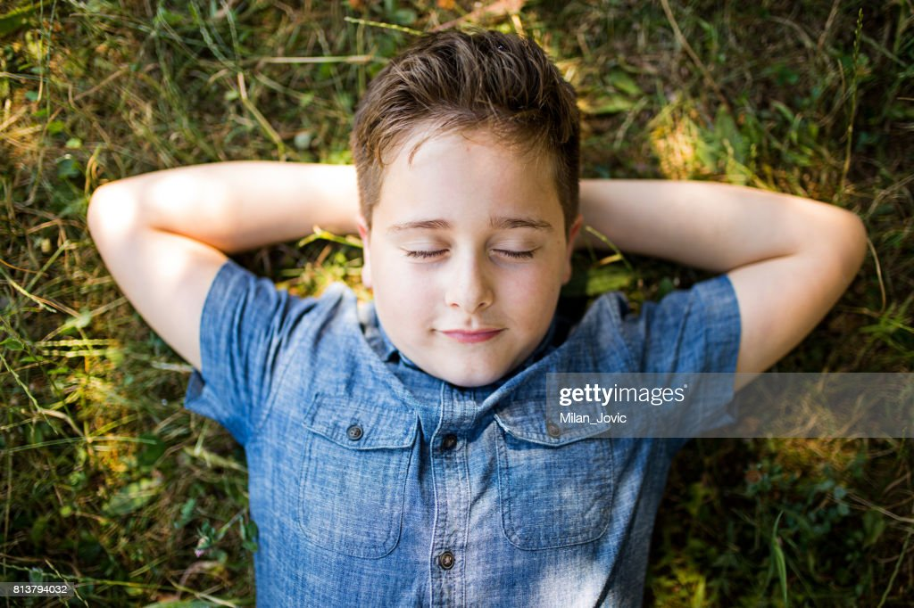 Boy with headphones listening to music in park : Stock Photo