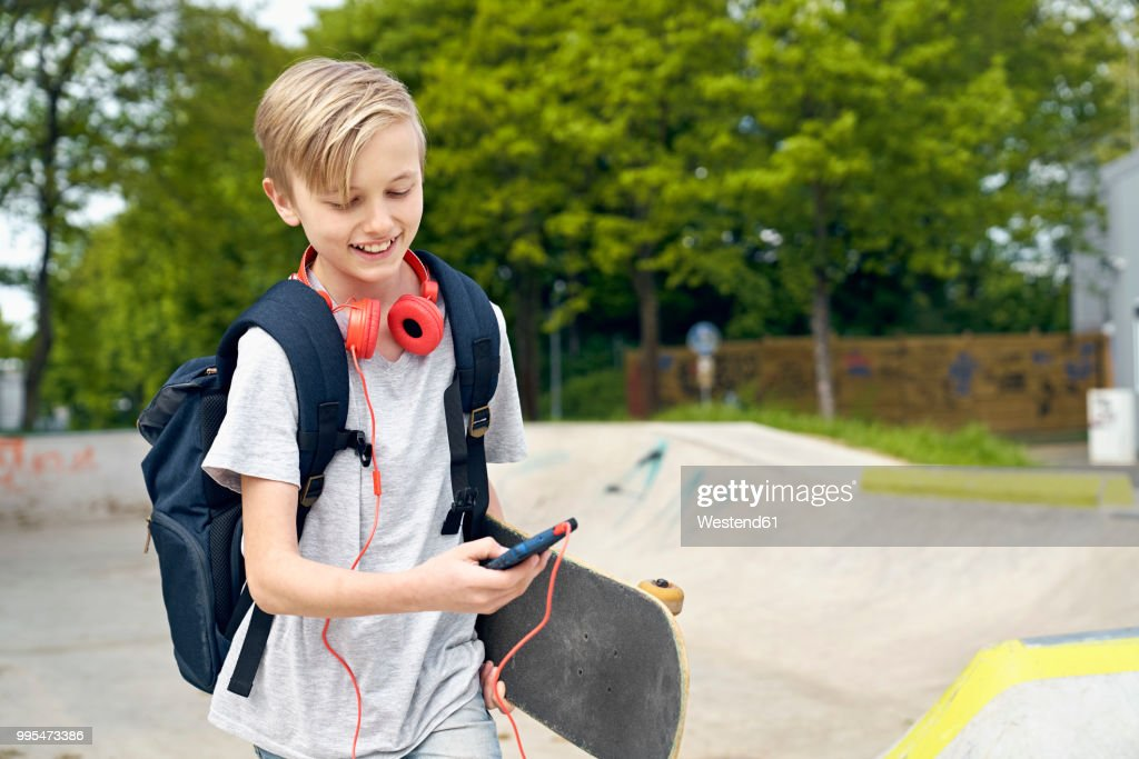 Boy with headphones, skateboard and school bag using smartphone : Foto de stock