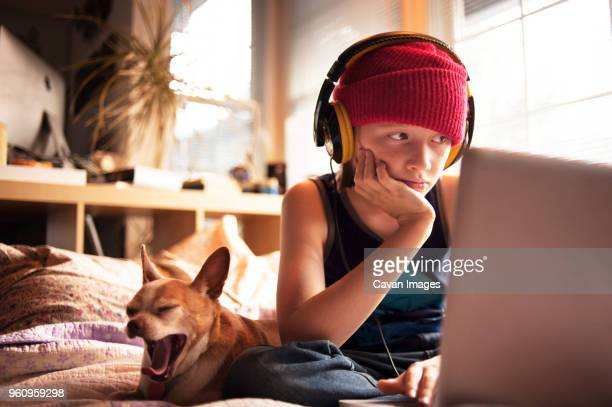 Boy with headphones using laptop on bed at home