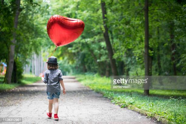boy with heart shape balloon - innocence stock pictures, royalty-free photos & images
