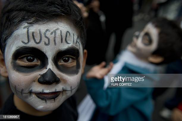 A boy with his face painted accompanies his mother in a demonstration in front of the Mexican Electoral Tribunal building while inside a plenary...