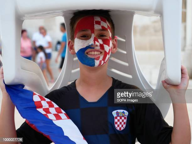 A boy with his face painted is seen carrying a seat on his head Croatians in the Island of Pag watched the world cup football final match Croatia vs...