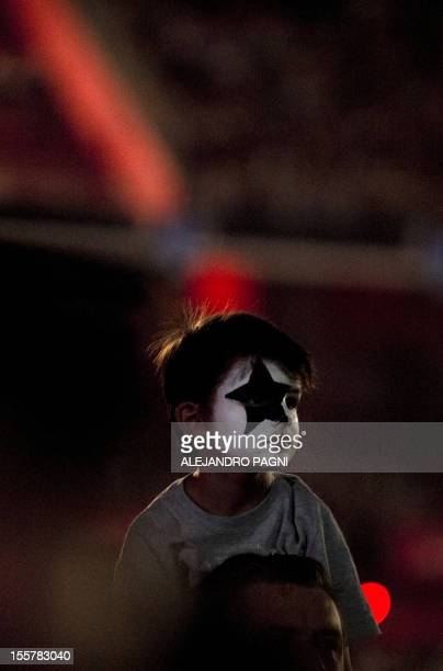 A boy with his face painted waits for the appearance of US hardrock band Kiss during their Monster Tour 2012 concert at River Plate Stadium in Buenos...