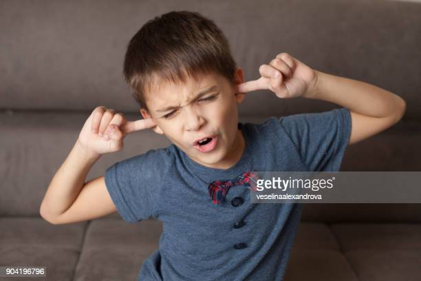 boy with his fingers in his ears - fingers in ears stock pictures, royalty-free photos & images