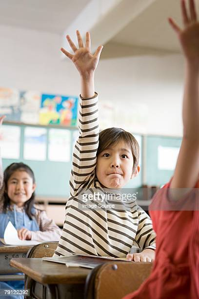 A boy with his hand raised