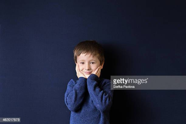 boy with his hands on his face