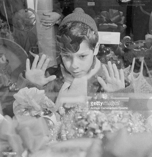 A boy with his nose and hands pressed against the window of a sweet shop Rome circa 1960