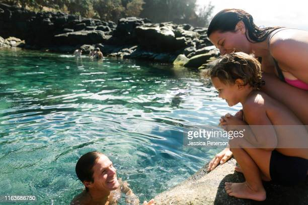 boy with his parents by tide pool - sea swimming stock photos and pictures