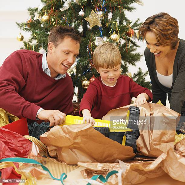 Boy (5-6) with his parents opening his Christmas present