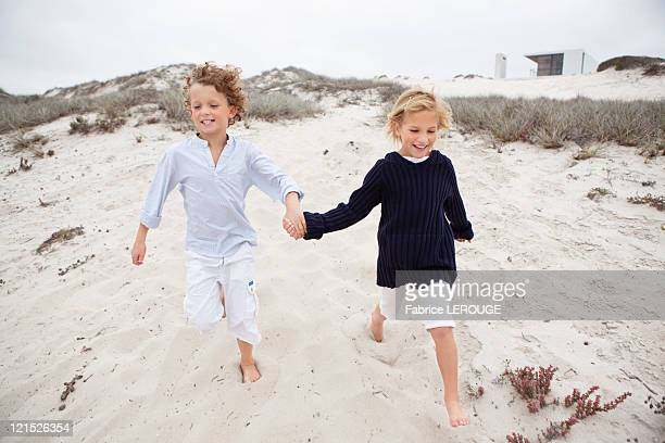 Boy with his sister holding hands and running on sand