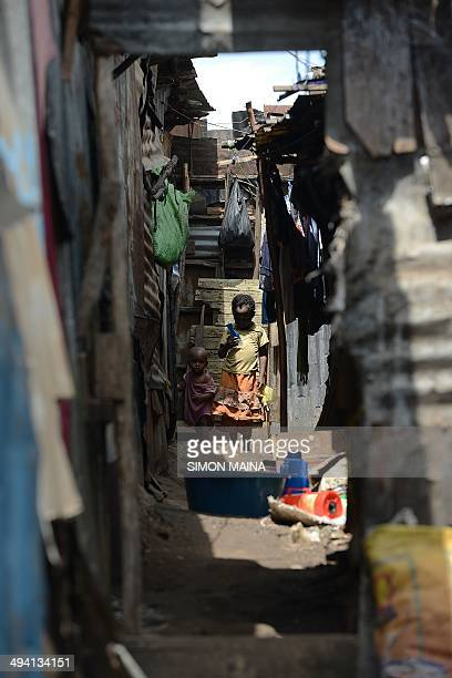 A boy with his sister walk outside their house on May 28 2014 in Mathare one of the poorest slums in Nairobi Running water and electricity are scarce...
