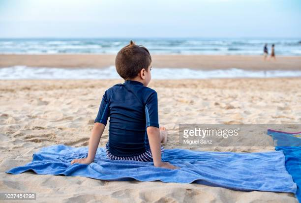 boy with his wetsuit sitting on the beach - towel stock pictures, royalty-free photos & images