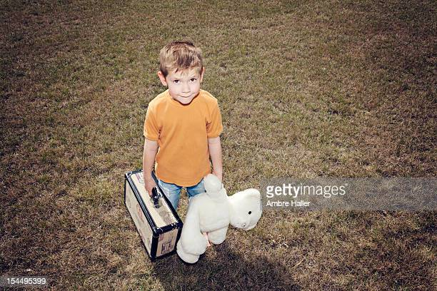 Boy with holding suitcase and teddy