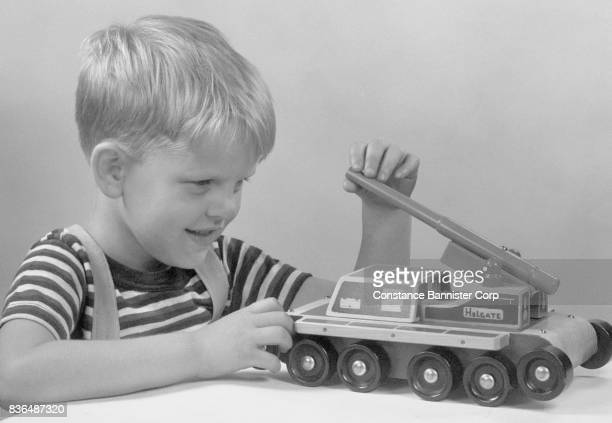 blond boy playing with toy tank