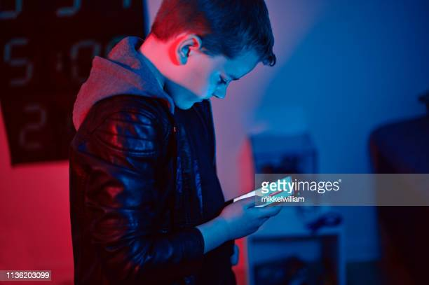 Boy with hoodie looks at screen on smart phone at night