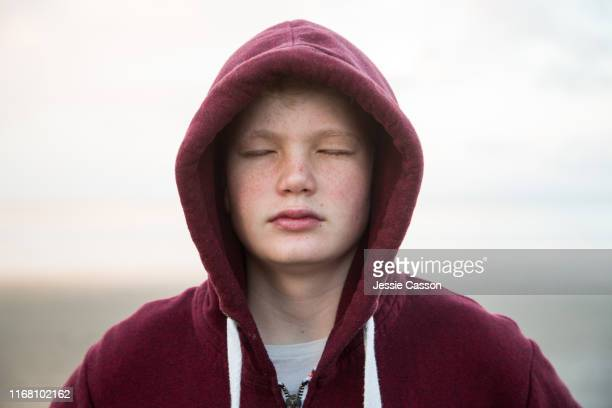 boy with hoodie on beautiful beach with eyes closed in evening light - condition stock pictures, royalty-free photos & images