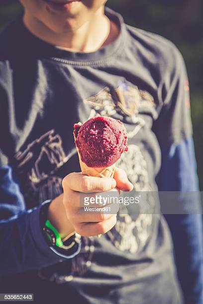 Boy with ice cream cone, partial view