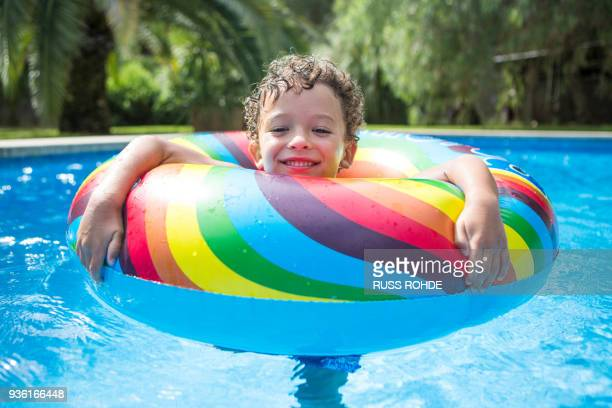 Boy with inflatable ring in outdoor swimming pool, portrait