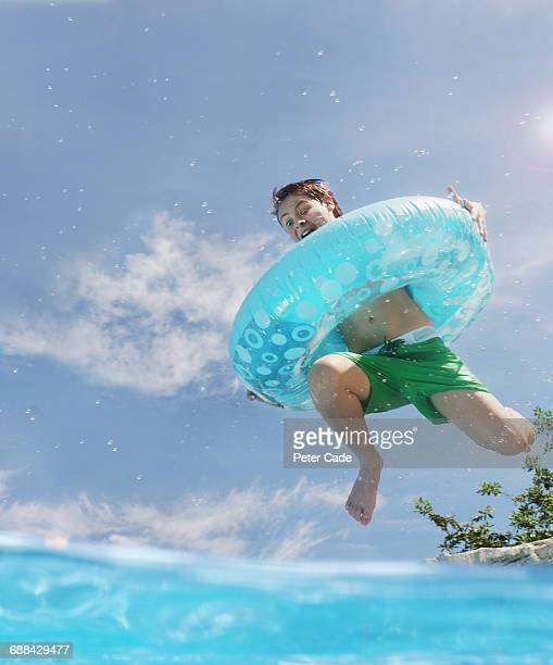 Boy with inflatable ring jumping into pool