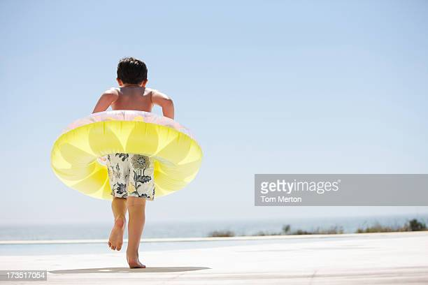 boy with inflatable ring stepping out of infinity pool - very young tube stock photos and pictures