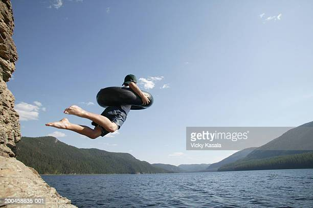 Boy (10-12) with inner tube jumping off rock into lake, side view