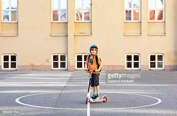 boy with kick scooter on schoolyard, stockholm, sweden - patio de colegio fotografías e imágenes de stock