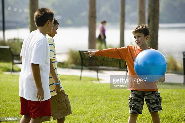 Boy with large blue ball playing with and giving instructions his friends