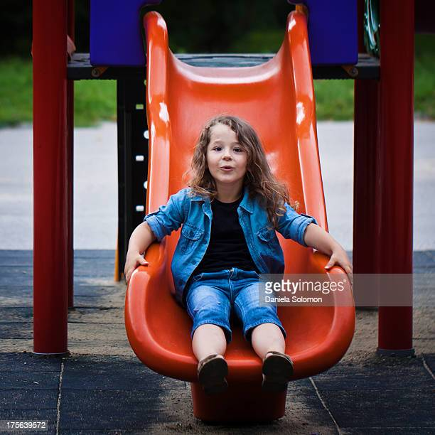 Boy with long curly hair getting down to the slide