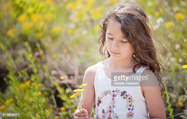 Boy with long hair in the meadow holding flowers