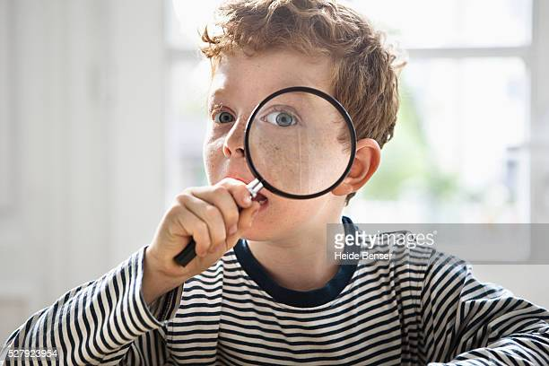boy (7-9) with magnifying glass - 虫メガネ ストックフォトと画像