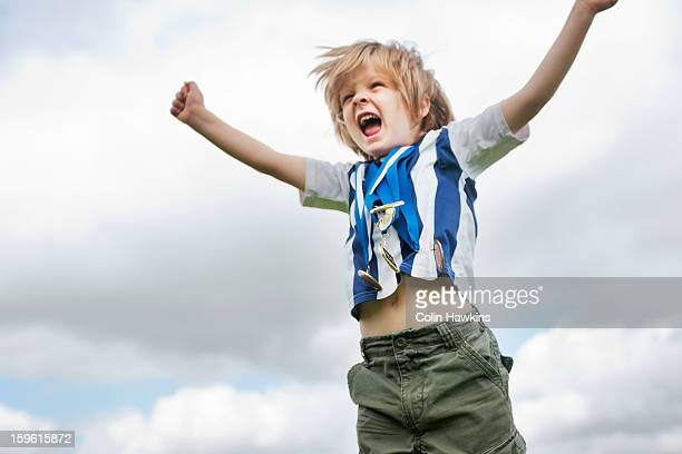 boy with medals cheering outdoors - medalist stock pictures, royalty-free photos & images