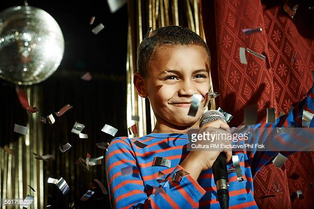 Boy with microphone waving on stage