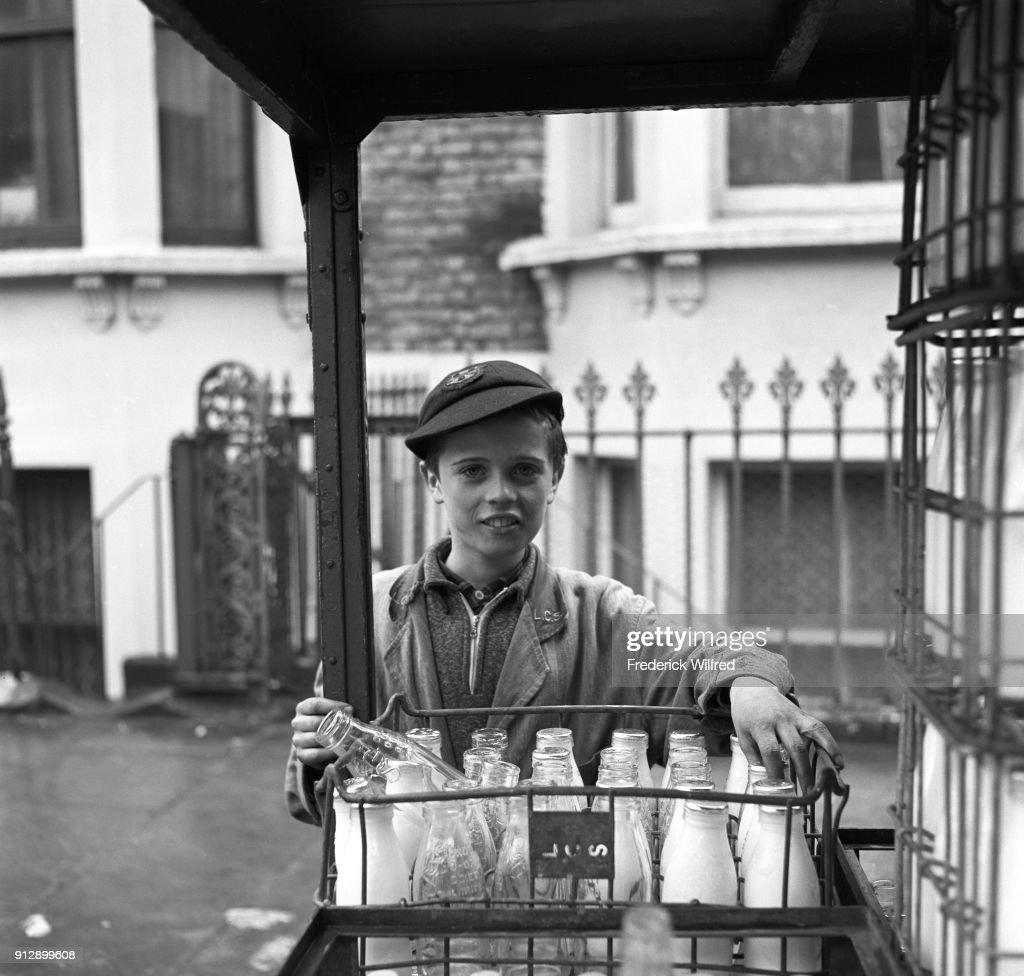 Boy with milk bottles : News Photo