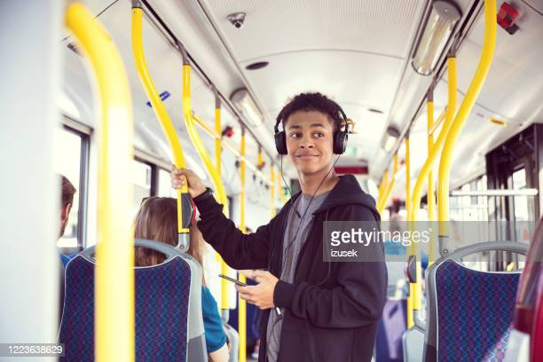 boy with mobile phone traveling in bus - african ethnicity stock pictures, royalty-free photos & images