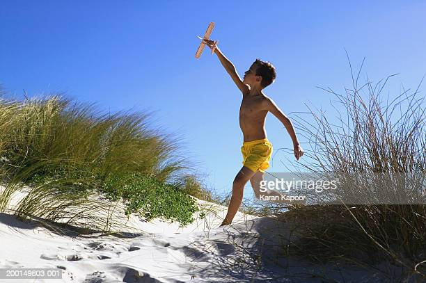 Boy (8-10) with model aeroplane running along grassy sand dunes