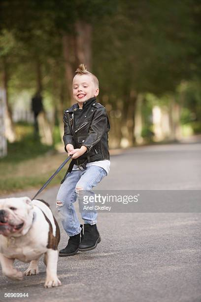 Boy with mohawk in leather jacket walking dog