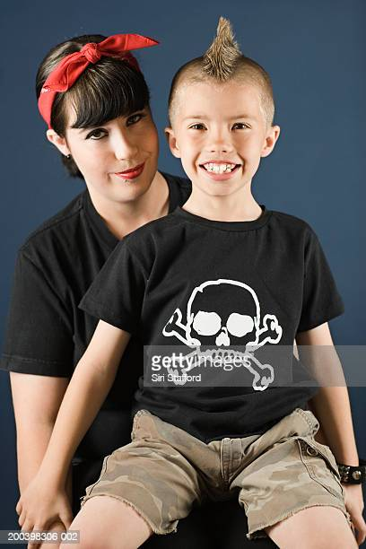 Boy (4-6) with mohawk sitting on mother's lap