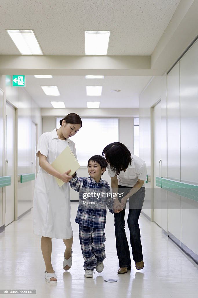 Boy (5-6) with mother and nurse in hospital corridor : Foto stock