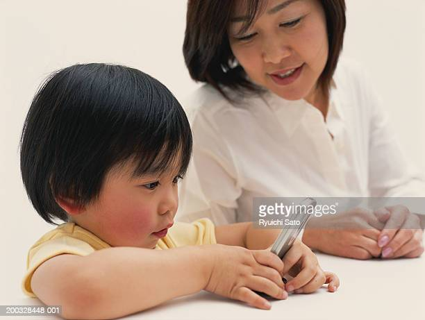 Boy (3-4) with mother looking at mobile phone