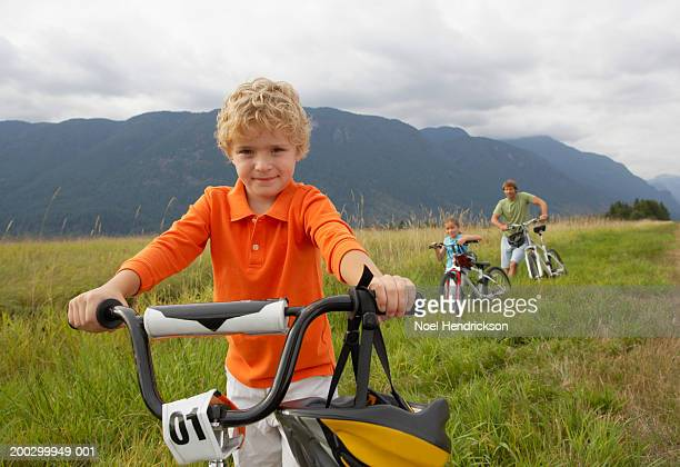 Boy (5-7 years) with mountain bike, smiling, portrait