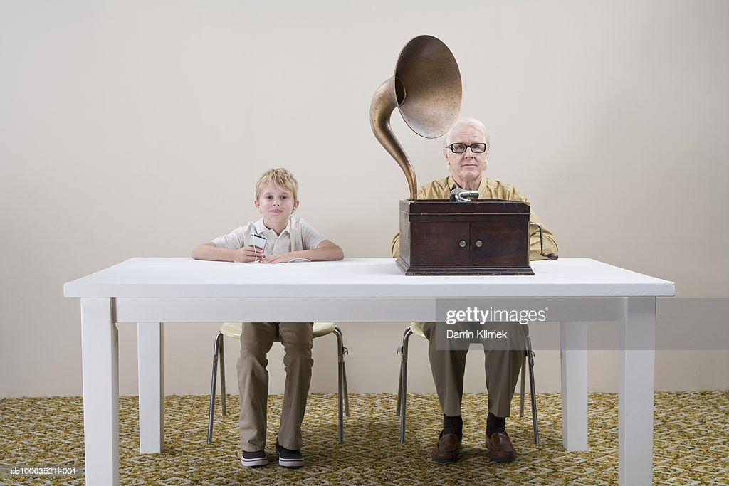 Boy (10-11) with mp3 player and man with gramophone sitting at table : Stock Photo