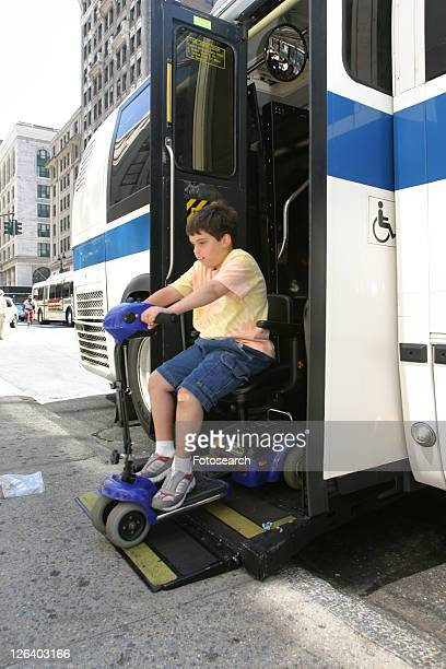 Boy with Muscular Dystrophy, utilizing a scooter/cart for mobility, exiting a city bus via a chair lift.