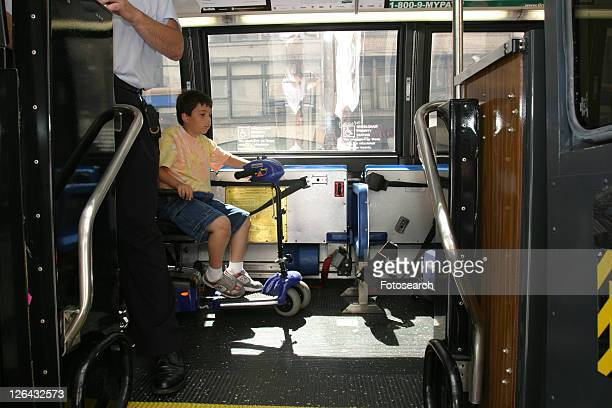 Boy with Muscular Dystrophy, utilizing a scooter/cart for mobility, using a city bus.