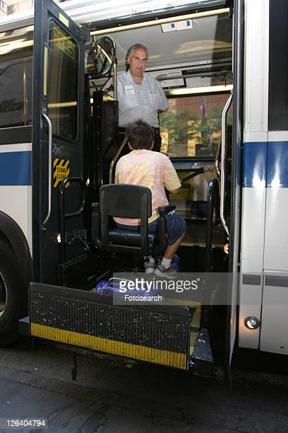 Boy with Muscular Dystrophy, utilizing a scooter/cart for mobility, getting on a city bus via a chair lift.