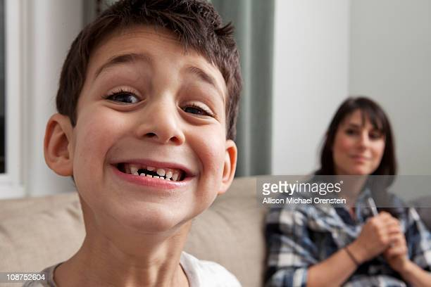 boy with no teeth smiling with mom in background