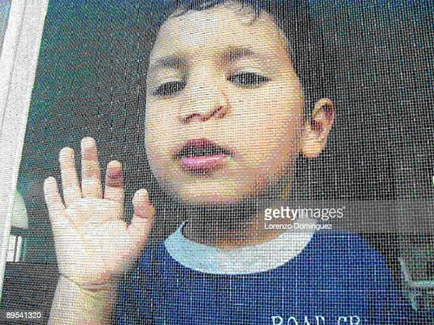 Boy with nose pressed against screen door